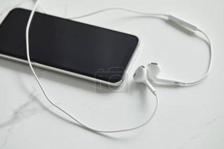 Foto de Smartphone con pantalla en blanco y auriculares con cable sobre superficie de mármol blanco - Imagen libre de derechos