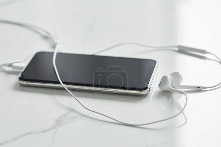 Photo pour Mise au point sélective du smartphone avec écran blanc et écouteurs câblés sur la surface blanche - image libre de droit