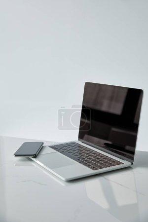 Photo pour Ordinateur portable et Smartphone avec écran blanc sur la surface blanche d'isolement sur le gris - image libre de droit
