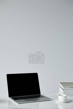 Photo for Laptop with blank screen, coffee up and stacked journals isolated on grey - Royalty Free Image
