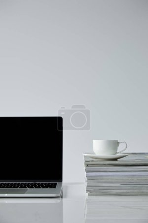 Photo pour Ordinateur portable avec écran blanc et tasse à café sur pile de magazines d'isolement sur le gris - image libre de droit