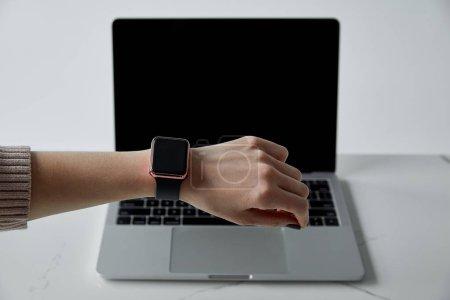Photo pour Vue partielle de femme dans la montre intelligente et l'ordinateur portatif avec l'écran blanc isolé sur le gris - image libre de droit