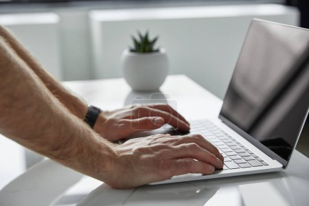 Photo for Partial view of man using laptop on table with flowerpot - Royalty Free Image