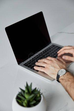 Photo pour Partie de vue de l'homme utilisant l'ordinateur portatif avec l'écran blanc isolé sur le gris - image libre de droit