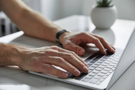 Photo for Cropped view of man using laptop with black keypad on white marble table - Royalty Free Image