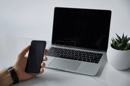 Photo pour Vue partielle de l'homme retenant le smartphone, ordinateur portatif avec l'écran blanc et le pot de fleurs sur le gris - image libre de droit