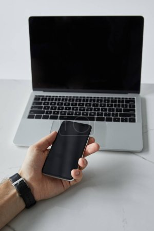 Photo pour Vue recadrée de l'homme retenant le smartphone et l'ordinateur portable avec l'écran blanc isolé sur le gris - image libre de droit
