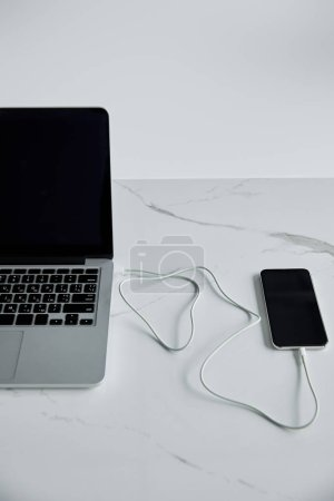Photo for Smartphone connected with cable to laptop with blank screen isolated on grey - Royalty Free Image