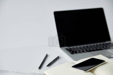 Photo pour Focus sélectif de Notebook, smartphone et ordinateur portable avec écran blanc isolé sur le gris - image libre de droit