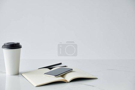 Photo pour Tasse jetable, smartphone avec écran blanc isolé sur le gris - image libre de droit