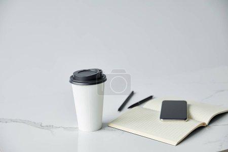 Photo pour Smartphone avec écran blanc, ordinateur portable et tasse jetable isolé sur le gris - image libre de droit