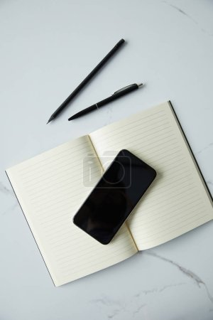 Photo for Top view of smartphone with blank screen, notebook, pen and pencil on white marble surface - Royalty Free Image