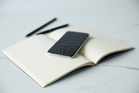 Photo for Selective focus of smartphone with blank screen on notebook, pen and pencil on white surface - Royalty Free Image