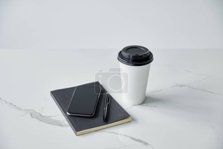 Photo for Smartphone with blank screen, black notebook, pen and paper cup isolated on grey - Royalty Free Image