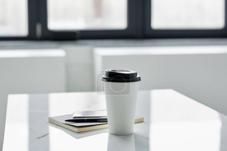 Photo for Selective focus of paper cup, notebook and pen on white table in sunlight - Royalty Free Image