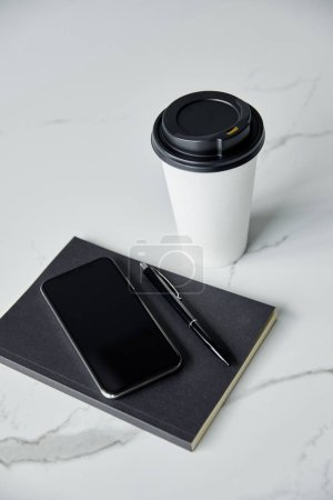 Photo for Disposable cup, smartphone with blank screen, black notebook and pen on white marble surface - Royalty Free Image