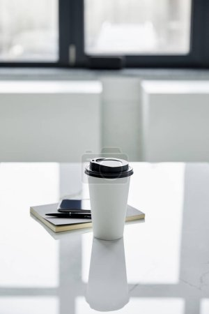 Photo for Disposable cup, smartphone with blank screen, notebook and pen on white table - Royalty Free Image