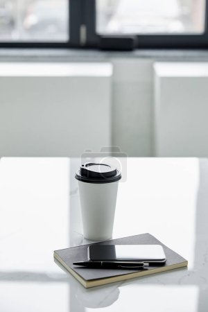Photo for Smartphone with blank screen, notebook, pen and disposable cup on white table - Royalty Free Image
