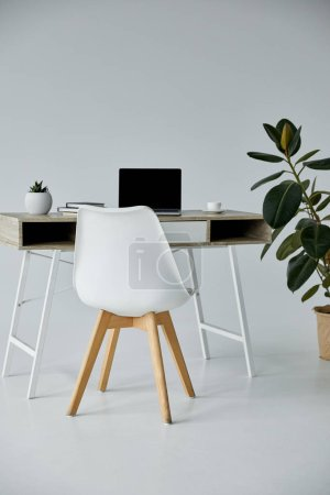 Photo for White chair, table with laptop, books, ficus in flowerpot on grey - Royalty Free Image