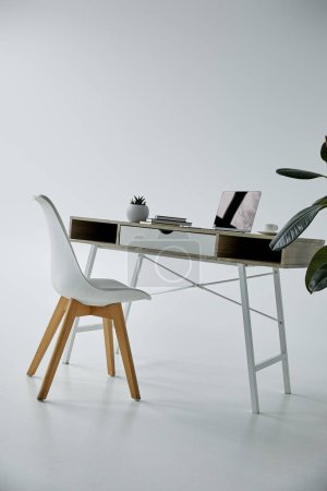 Photo pour Table de travail avec ordinateur portable, livres, et chaise blanche sur le fond gris - image libre de droit