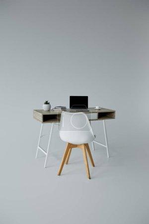 Foto de Silla blanca, mesa con laptop, libros y maceta sobre fondo gris - Imagen libre de derechos