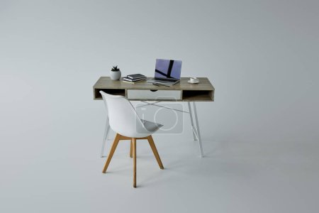 Foto de Silla blanca, mesa con libros y Laptop sobre fondo gris - Imagen libre de derechos