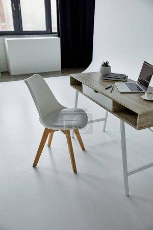 Foto de Silla blanca y mesa con laptop, libros, maceta y taza de café en blanco - Imagen libre de derechos