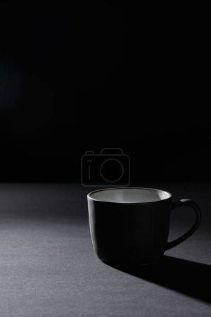 Photo for Coffee cup on dark textured surface on black - Royalty Free Image