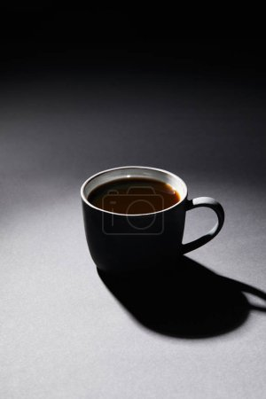 Photo for Full cup of coffee on dark textured surface - Royalty Free Image