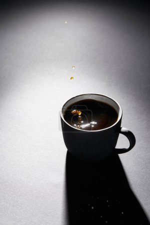 Photo for Cup full of coffee with drops on dark textured surface - Royalty Free Image