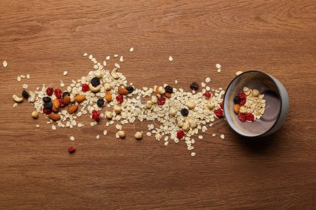 Photo for Top view of oat flakes scattered with nuts and dried berries near bowl at wooden table - Royalty Free Image
