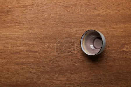 Photo for Top view of empty ceramic bowl at wooden table with copy space - Royalty Free Image