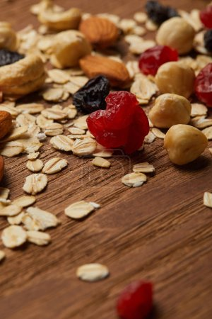 Photo for Close up of oat flakes with dried berries and hazelnuts on wooden table - Royalty Free Image