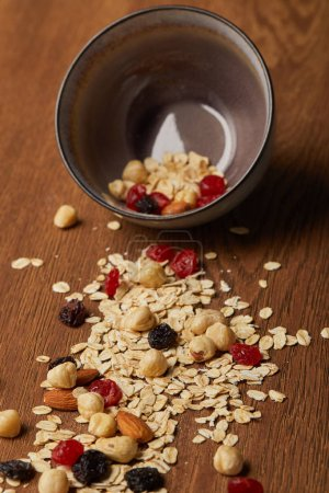 Photo for Oat flakes scattered with nuts and dried berries from bowl on wooden table - Royalty Free Image
