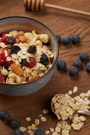 Photo for Close up of berries, nuts and muesli in bowl for breakfast on wooden table - Royalty Free Image