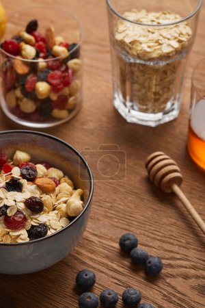 Photo for Selective focus of cereal in bowl with nuts and dried berries prepared for breakfast - Royalty Free Image