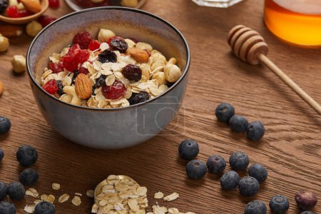 Photo for Cereal in bowl with nuts and dried berries prepared for breakfast on wooden table - Royalty Free Image