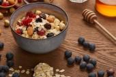 """Постер, картина, фотообои """"Каша в миске с орехами и сушеными ягодами, приготовленную на завтрак на деревянном столе"""""""