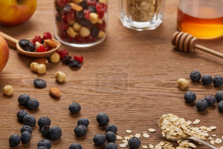 Photo for Selective focus of oat flakes, nuts, honey and berries on wooden table with copy space - Royalty Free Image