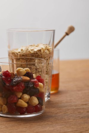 Photo for Glasses with dried berries, nuts, oat flakes on wooden table isolated on grey - Royalty Free Image