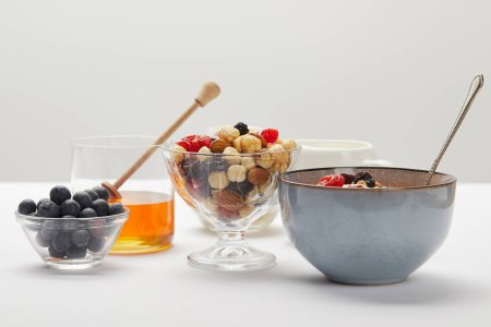Photo for Bowls and glasses with berries, nuts, honey and cereal served for breakfast on white table isolated on grey - Royalty Free Image