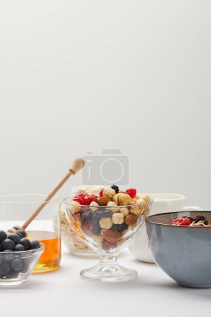 Photo for Bowls with berries, nuts, honey and cereal served for breakfast on white table isolated on grey - Royalty Free Image