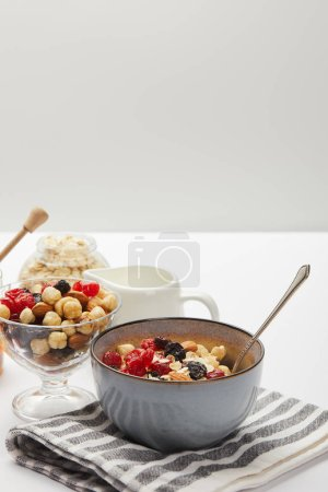 Photo for Bowls with berries, nuts, honey and oat flakes served for breakfast on white table isolated on grey - Royalty Free Image
