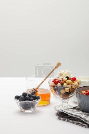Photo pour Muesli avec baies, noix et miel dans des bols servis pour le petit déjeuner sur table blanche d'isolement sur le gris - image libre de droit
