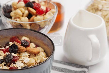 Photo for Selective focus of bowl on striped napkin with oat flakes, nuts and berries near milk jug - Royalty Free Image
