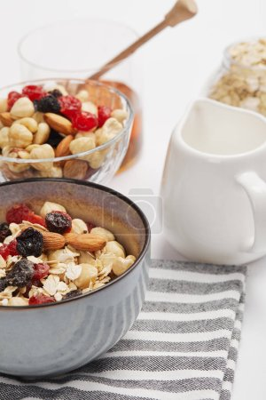 Photo for Selective focus of bowl on striped napkin with oat flakes, nuts and berries near white milk jug - Royalty Free Image
