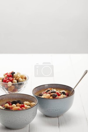 Photo for Bowls with muesli, dried berries and nuts served for breakfast isolated on grey - Royalty Free Image