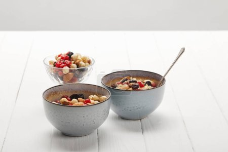 bowls with muesli, dried berries and nuts served for breakfast on white table isolated on grey
