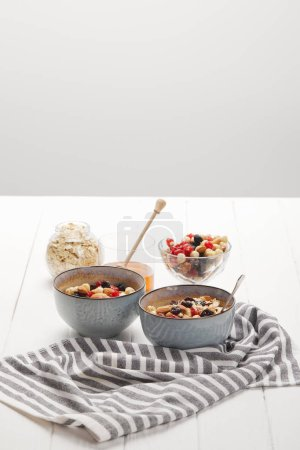 Photo for Bowls with muesli, dried berries and nuts served for breakfast with honey isolated on grey - Royalty Free Image