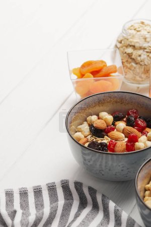 Photo for Bowls with muesli, dried berries and nuts served for breakfast with dried apricots on white wooden table with copy space - Royalty Free Image